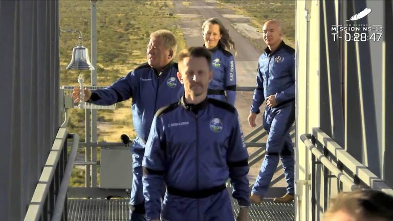 Os quatro integrantes da missão caminham enfileirados; ator é o segundo, e toca com a mão direita um sino que está na lateral do corredor