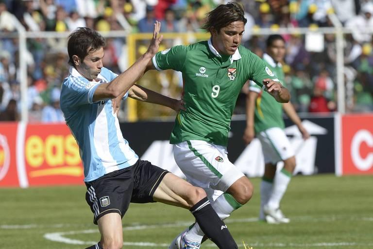 Marcelo Moreno passa por Basanta, da Argentina, em partida pelas eliminatórias para a Copa de 2014