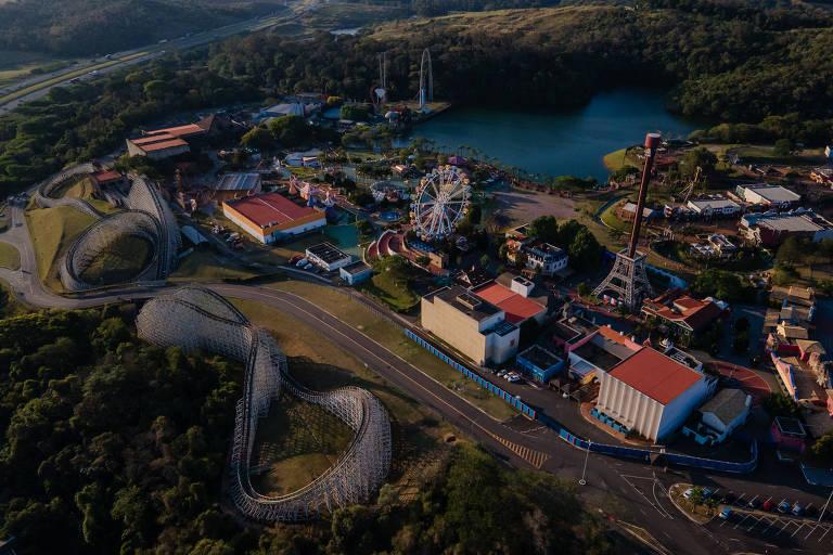 Parque temático visto de cima, com montanha-russa, roda-gigante e um lago