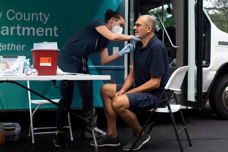 Homem de bermuda e camiseta está sentado, de perfil, enquanto recebe dose de vacina no braço direito