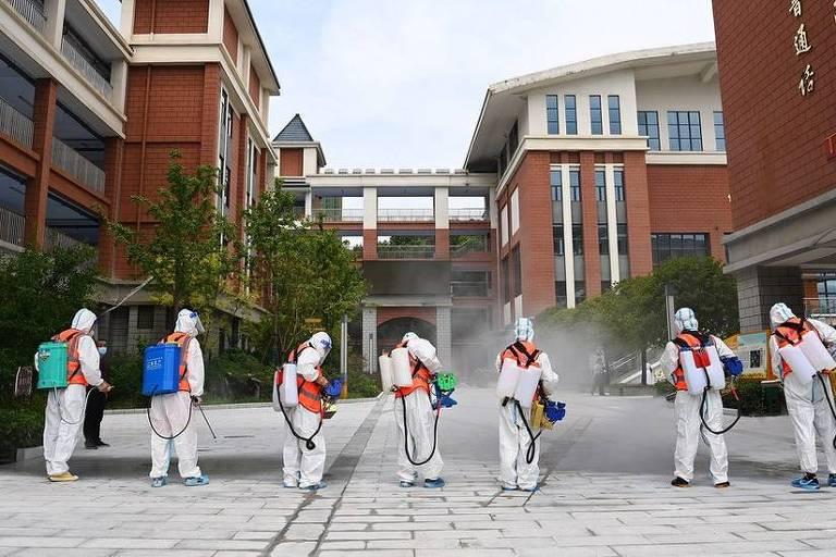 Um grupo de pessoas usando roupa branca dos pés a cabeça está enfileirada e de costas. Eles estão com um equipamentos nas costas e segurando uma mangueira. Ao fundo, se vê um prédio.