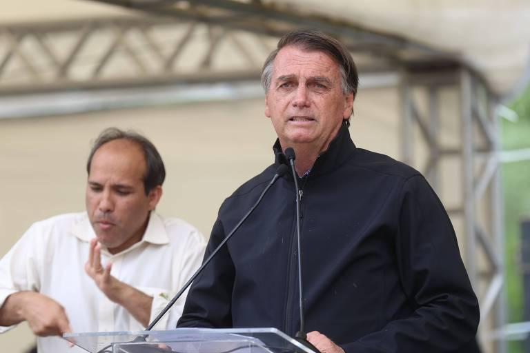 Bolsonaro usa casaco preto e discursa em um microfone apoiado em um pedestal transparente. Atrás um intérprete de libras gesticula.