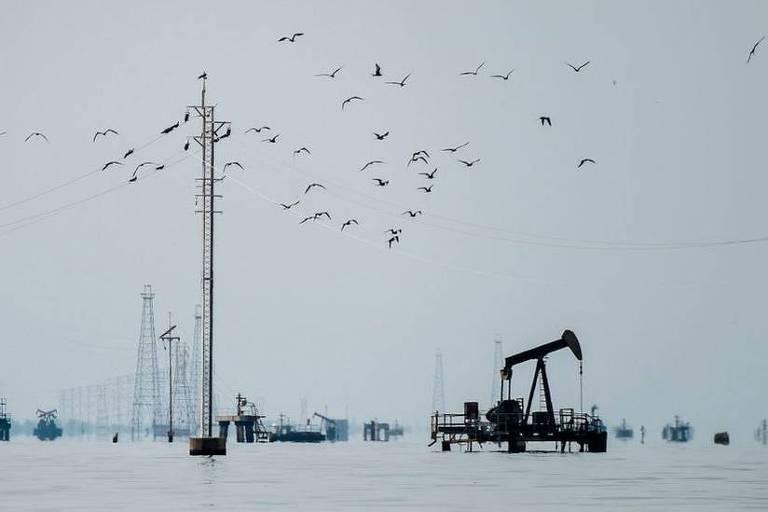 Imagem mostra lago com plataformas e instalações petrolíferas