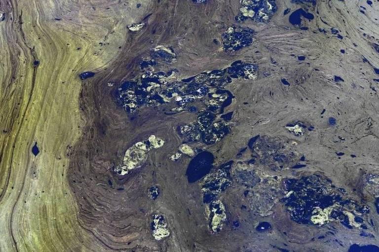 Imagem aérea mostra derramamento de óleo em um lago