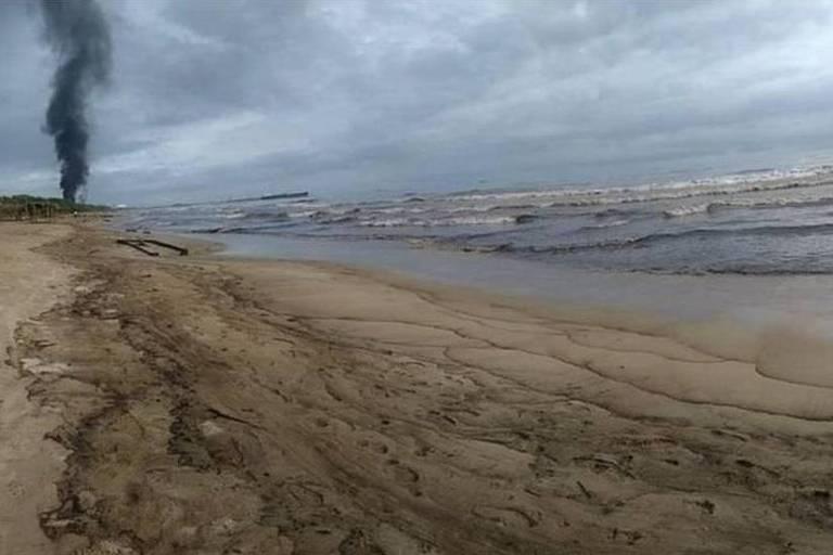 Imagem mostra uma praia com a areia suja de óleo. Ao fundo, se vê uma fumaça preta