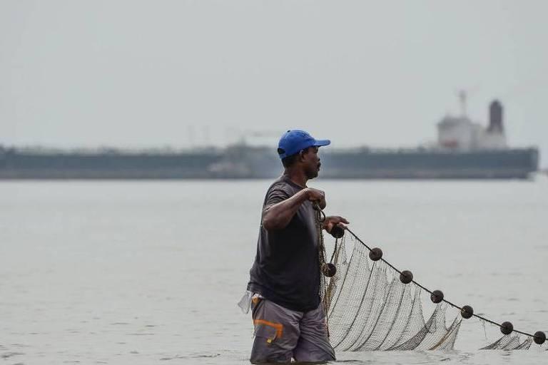 Em destaque, um pescador segurando uma rede está dentro da água. Ao fundo, se vê uma grande embarcação.