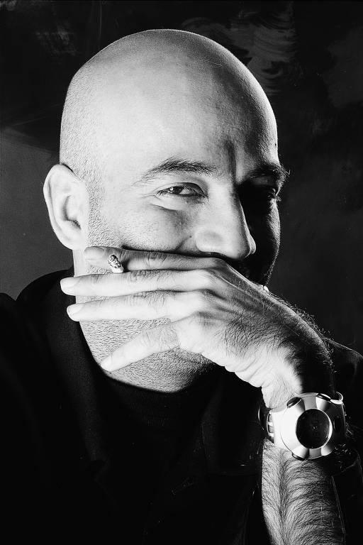 Homem com mãos em frente ao rosto sorri. Foto em preto e branco