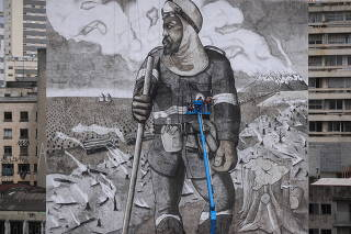 Brazilian artist and activist Mundano works on the mural 'The Forest Brigade,' in Sao Paulo