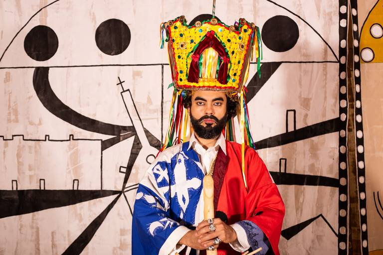 Um homem vestindo um manto azul e vermelho e uma coroa colorida