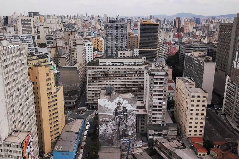 Inúmeros prédios cinzentos na região central de São Paulo; ao centro deles, o mural cinza do artista