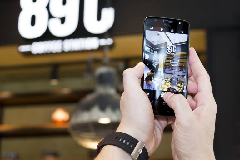 Um homem segura um celular e tira foto do letreiro da cafeteria