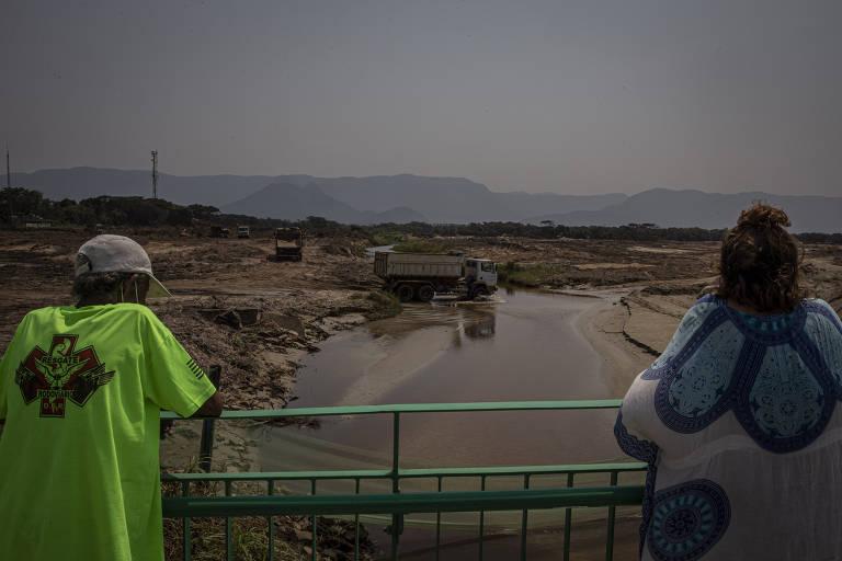 Um homem e uma mulher apoiados em uma grade olhando para canal de drenagem