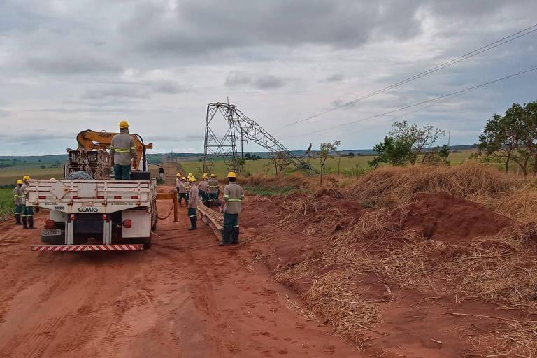 Homens em um caminhão trabalham perto de torre caída