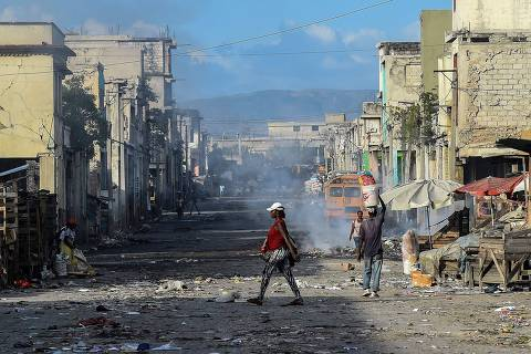 (FILES) In this file photo taken on December 20, 2019, eople walk on the deserted road ahead of gang shootings in downtown in Port-au-Prince. - Long confined to the slums, the gangs have gradually extended their control in Haiti and the nearly three million inhabitants of Port-au-Prince are forced to adapt their daily lives to this reality, for fear of being the next victim.