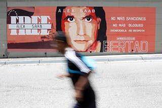 A man goes past a mural in support of the liberation of Colombian businessman and envoy Alex Saab, who is detained in Cape Verde on charges of laundering money for the government of Venezuelan President Nicolas Maduro, in Caracas