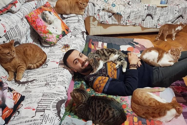 Sarper Duman na casa dele com alguns dos gatos que ele já resgatou