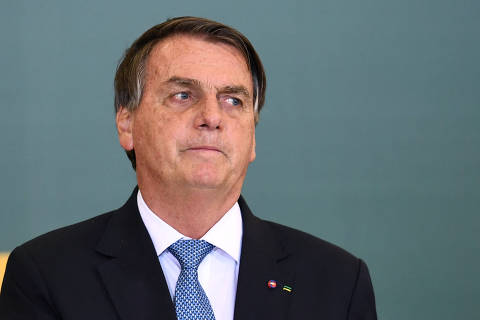 (FILES) In this file photo taken on October 07, 2021 Brazilian President Jair Bolsonaro gestures during the Ceremony for the Modernization of Occupational Health and Safety Regulations at the Planalto Palace in Brasilia. - Bolsonaro will get a new headache on October 19, 2021, since the rapporteur of the parliamentary commitee that investigates his handling of the COVID-19 pandemic will accuse him formally of several crimes. (Photo by EVARISTO SA / AFP) ORG XMIT: ESA1173