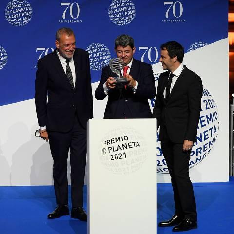 (From 2nd-L) Winners of Spain's 2021 Premio Planeta award Jorge Diaz, Antonio Mercero and Augustin Martinez receive the trophy for their novel