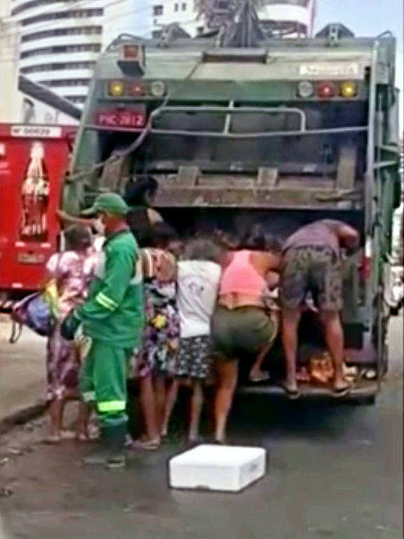 Pessoas buscam comida dentro de um caminhão de lixo que está parada na rua