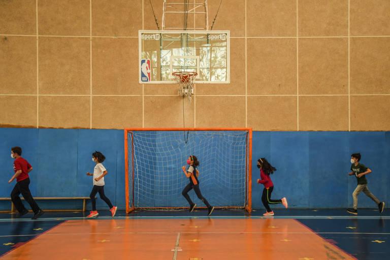 alunos correm com distanciamento na quadra esportiva