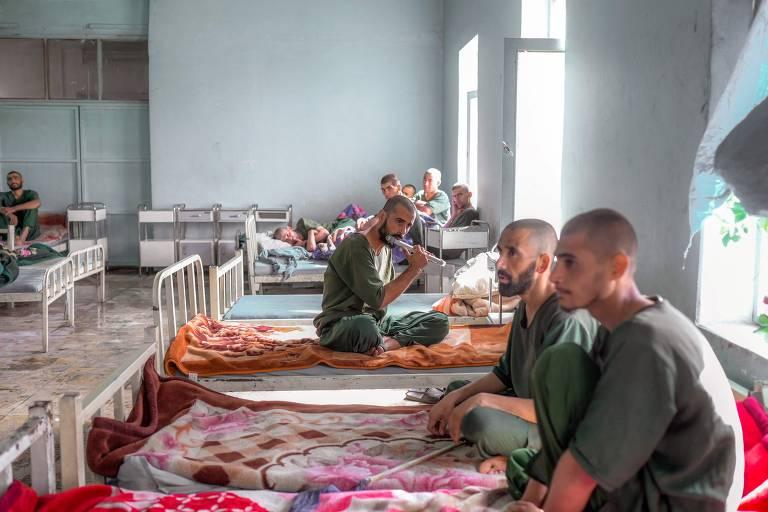 Dependente químico toca flauta ao lado de companheiros de dormitório em centro de reabilitação de usuários de droga em Cabul