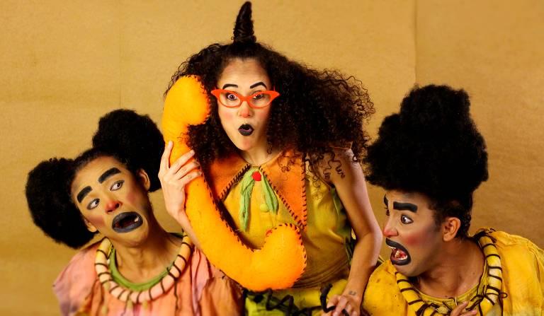 Três pessoas vestidas de amarelo e com cara de assustada, uma delas tem telefone gigante na mão