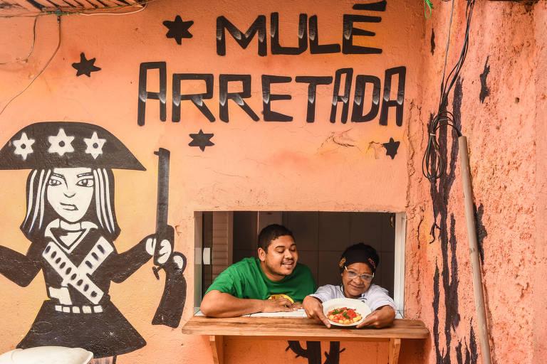 Thiago Vinícius de Paula da Silva, aparece na janelinha do restaurante ao lado da mãe, cozinheira conhecida como Tia Nice