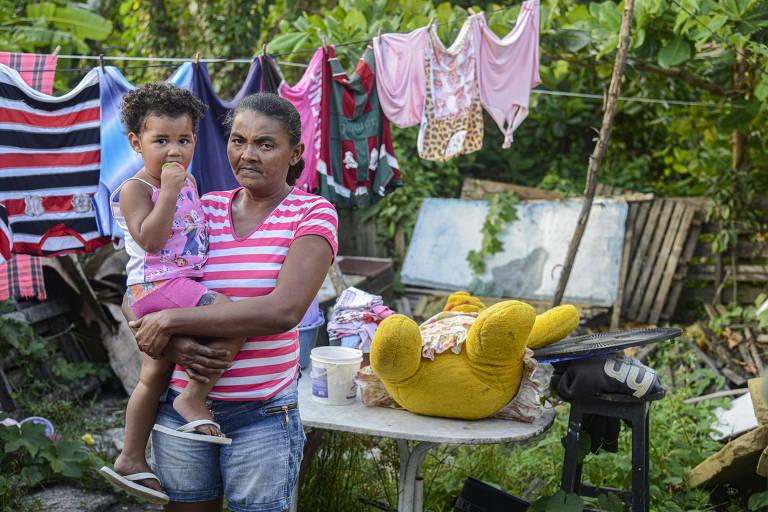 Ana Cristiane da Silva, 42, leva no colo Pamela da Silva, 2