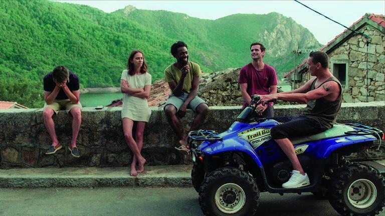 Quatro jovens sentados em um muro e outro em uma moto