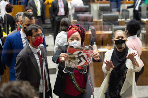 Vereadora Daiana Santos mostra o cartaz com simbolo nazista que os manifestantes contrários ao passaporte vacinal seguravam nas galerias
