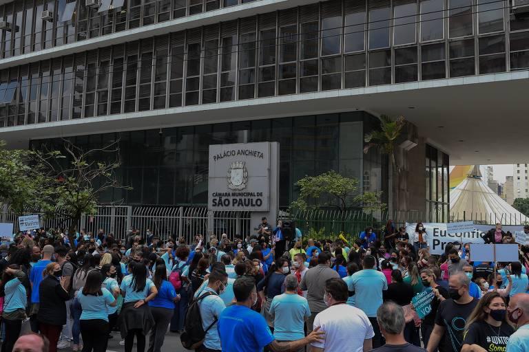 Manifestantes se reúnem na rua, diante do prédio da Câmara