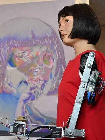 The world's first ultra-realistic AI robot artist, Ai-Da, who can draw, paint and is a performance artist, is pictured alongside her self-portrait during a press preview of the exhibition 'Ai-Da: Portrait of the Robot' at the Design Museum in London, on May 14, 2021. - Ai-Da is a life-size humanoid robot named after Ada Lovelace, the pioneering female scientist and mathemitician. As a machine with AI capabilities, her artist persona is the artwork, along with her drawings, performance art and collaborative paintings and sculptures. (Photo by Glyn KIRK / AFP) / RESTRICTED TO EDITORIAL USE - MANDATORY MENTION OF THE ARTIST UPON PUBLICATION - TO ILLUSTRATE THE EVENT AS SPECIFIED IN THE CAPTION
