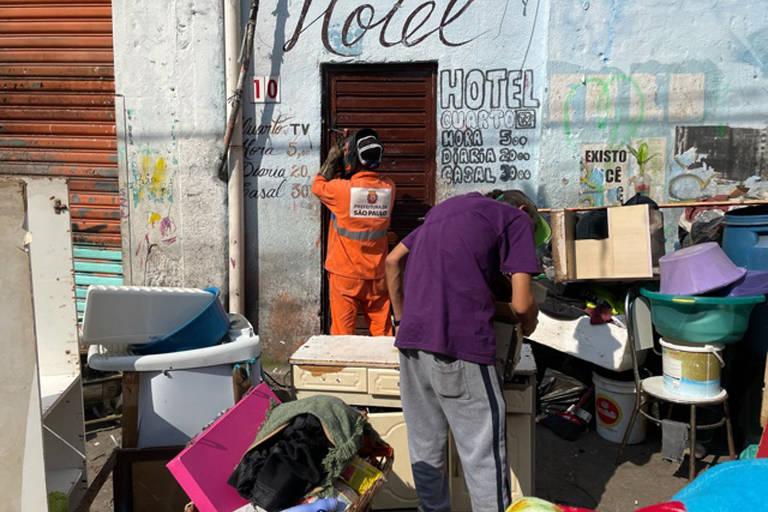 Homem com macacão laranja veda entrada de hotel com tijolos
