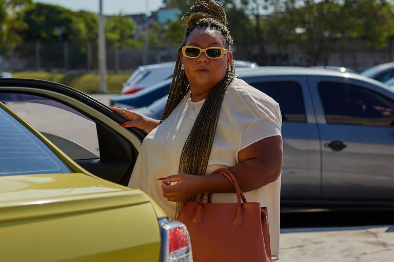 Mulher negra usando óculos de sol, bolsa de couro e roupa branca aparece abrindo a porta de um táxi. Ao fundo, um estacionamento com carros.