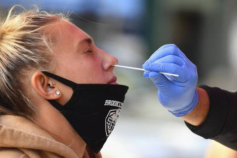 (FILES) In this file photo a health care worker takes a nasal swab sample from a student to test for Covid-19 at the Brooklyn Health Medical Alliance urgent care pop up testing site as infection rates spike on October 8, 2020 in New York City. - New York state will require all