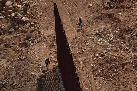 TOPSHOT - A group of Brazilian migrants cross the US-Mexico border in Otay Mesa, California on August 13, 2021. - An