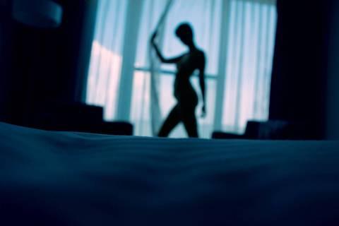 Mulher nua, na penumbra, de pé, próxima a uma janela com a cortina fechada