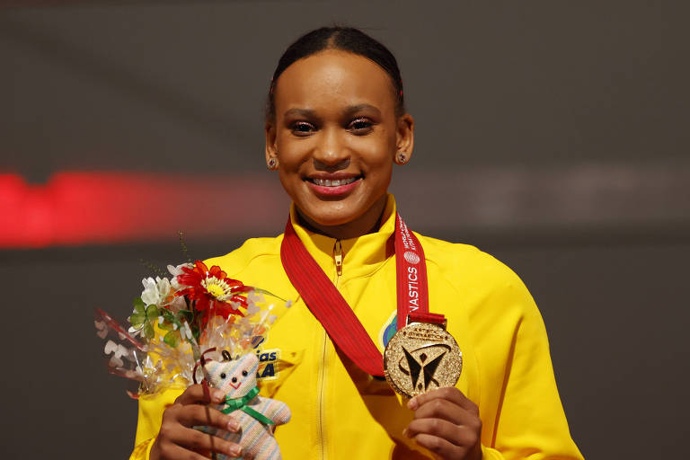 Rebeca, com agalho amarelo, sorri mostrando a medalha de ouro