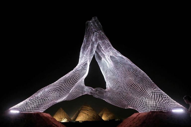 Instalação de mãos de luz brilhantes à noite em frente a pirâmides
