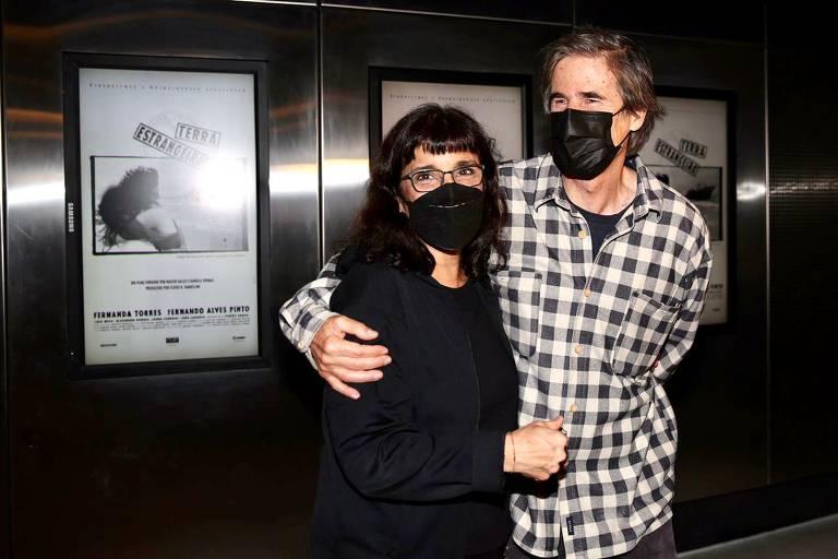 Daniela Thomas está em pé vestida de preto com máscara preta e abraçada ao cineasta Walter Salles, em pé de camisa xadrez e máscaras