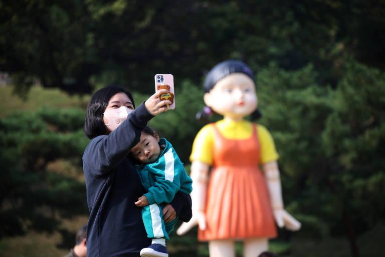 Mulher segura filho enquanto tira selfie com boneca de fundo