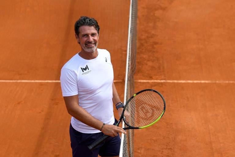 Mouratoglou, com camiseta branca e shorts escuro, possa para foto apoiado na rede de uma quadra de saibro