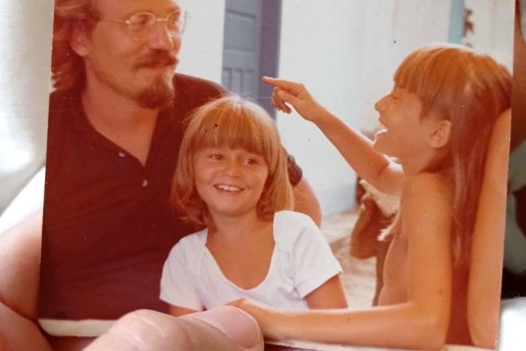 uma pessoa segura uma fotografia em que está um homem, à esquerda, uma criança sentada em seu colo e outra do lado.