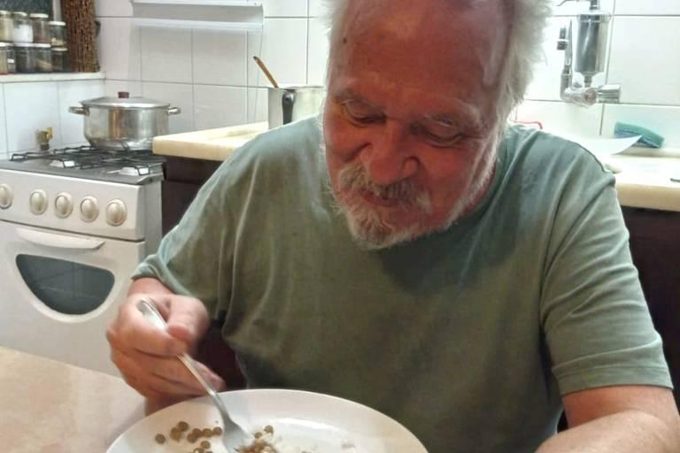 um homem idoso está sentado de frente para uma mesa segurando um garfo e olhando para um prato de comida.