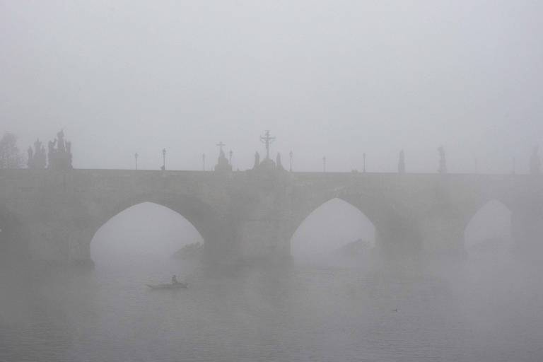 Sombra de arcos de ponte entrevistas entre névoa
