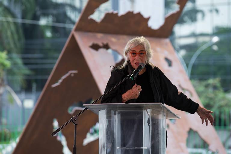 Imagem em primeiro plano mostra a artista Maria Bonomi falando de frente para um microfone. Ao fundo, se vê uma escultura