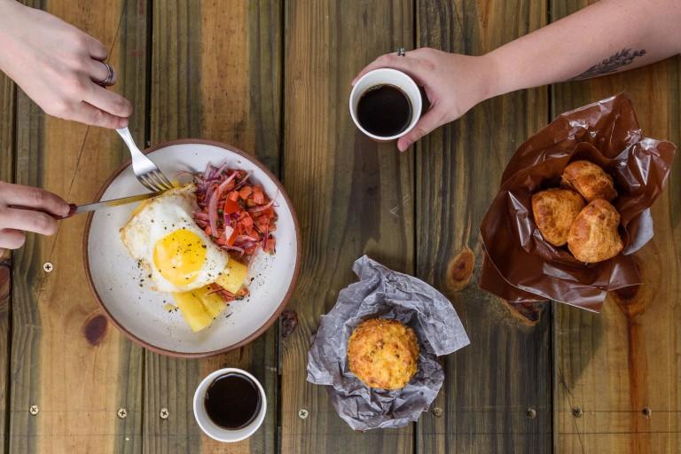 Visão de cima de um prato com ovo; pessoa usa garfo e faca nesse prato; outra pessoa segura um copo de café; há também mais dois cestos com alimentos e outro copo com café