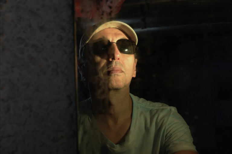 O cantor Zeca Baleiro posa para foto de boné e óculos escuros