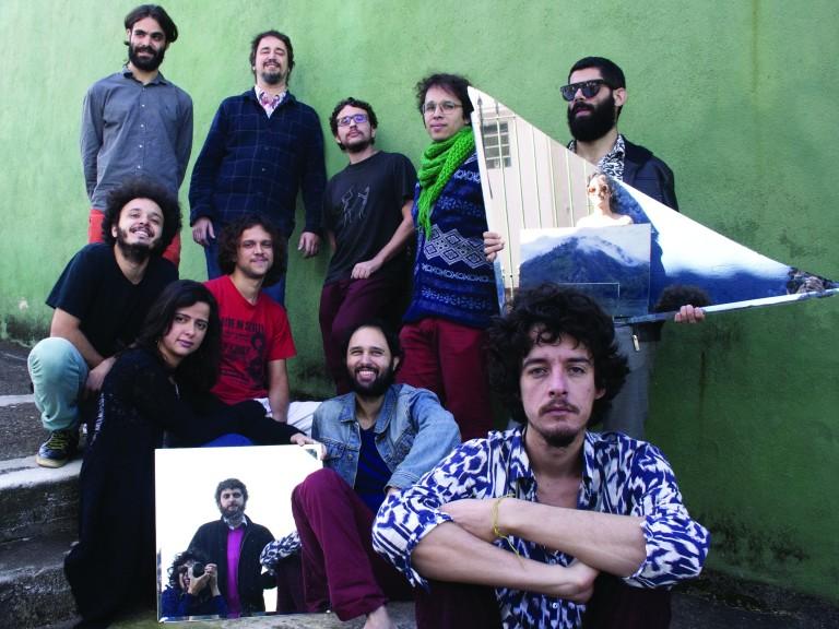 Integrantes da banda está sentados em uma escada segurando dois espelhos que refletem outros dois músicos do grupo