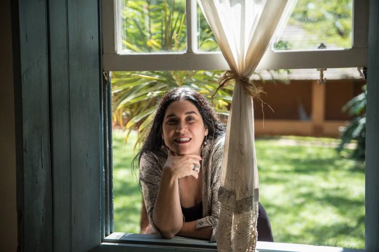 Monica Salmaso posa em janela com uma cortina na frente